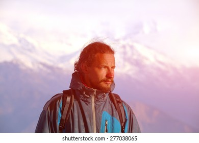 hiker at the top of a pass meeting the sunrise in the mountains