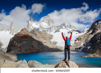 hiker at the top of a rock with his hands raised enjoy sunny day. Winner / Success concept