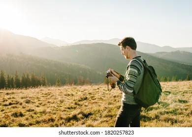 Wanderer Tourist in den Bergen bei Sonnenuntergang. Der Mensch fotografiert den Sonnenaufgang. Hipster mit Fotokamera und Rucksack reist und genießt die Natur.