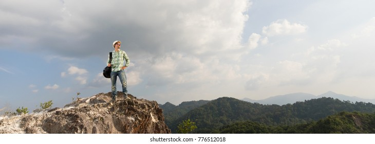 Hiker with  travel backpack on the top of mountain. Travel concept. Panoramic edition.