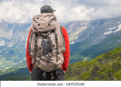 Hiker traveling in Alps. Alpine peaks landskape background. Jungfrau, Bernese highland. Sport, tourism and hiking concept.