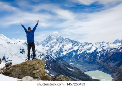 Hiker or traveller stands in winner pose at mountain top against mountains. Win or success concept