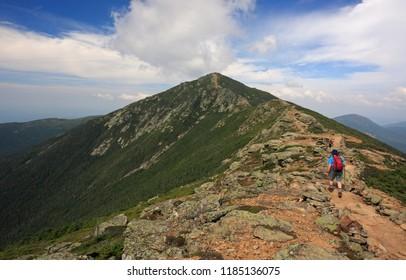 Hiker trekking along Franconia mountain ridge traverse, with a beautiful landscape background. Mount Lafayette, Mount Lincoln, New Hampshire, USA