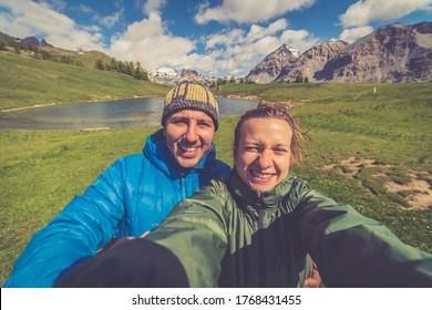 Wanderer wandern Mann und Frau, die sich vom Gipfel des Berges mit Tal- und Seeblick auf dem Hintergrund.