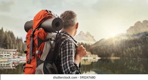 Hiker trekking on the mountains and contemplating the panorama, he is carrying a backpack and hiking equipment, sports and nature concept