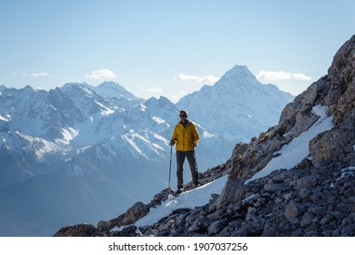 Hiker with trekking poles stands on the slope against the background of high snow-capped mountains
