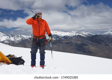 Hiker using walkie-talkie on snowy mountain peak