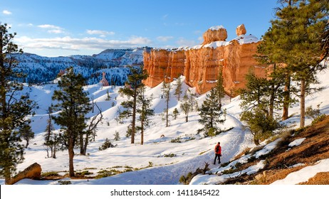 A hiker ventures along the snowy trails of Utah's Bryce Canyon National Park in winter.