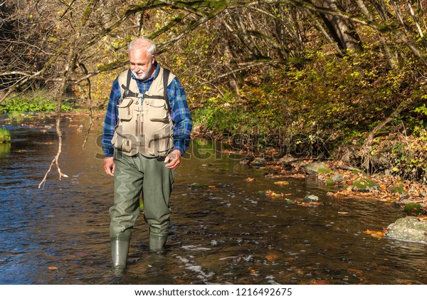 A hiker with a waders crosses the river Neckar in the Neckar valley between the villages of Dauchingen and Deisslingen. The Neckar Valley is a popular hiking and recreation area in the region.