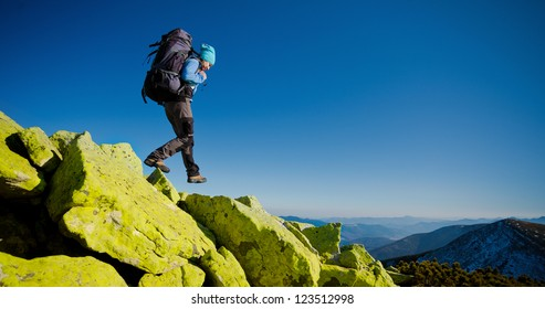 Hiker walking in autumn mountains. Caucasian model outdoors in nature