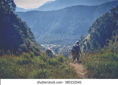 Hiker walking in the green mountains near Dakshinkali, Nepal