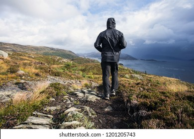 hiker walking in the mountains on a rainy day, goal succes and freedom. Travling Norway landscape beauty