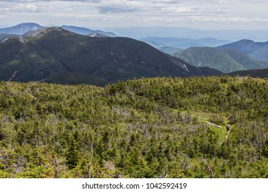 Hiker walking on beautiful mountain path with sweeping views into the Adirondack high peaks in New York
