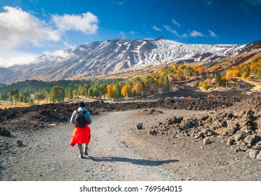 Hiker walking on a lavic path on northern side of Mount Etna - Shutterstock ID 769564015