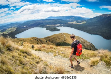 A hiker is walking on the Mount Robert Circuit in Nelson Lakes National Park, New Zealand.