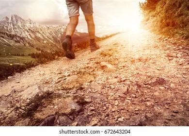 Hiker walking on mountain path.