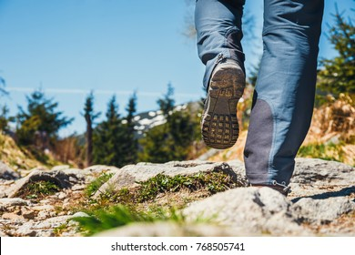 hiker walking on path in the mountains. Close up of shoes