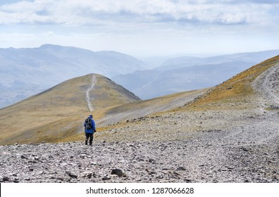 A hiker walking in the rocky mountains of the English Lake District, UK.