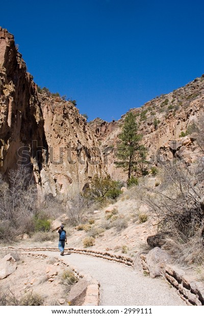 A hiker walks along the path to the ruins at Bandalier National Monument in central New Mexico.