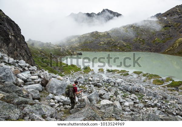 A hiker walks down a rocky slope toward a pastel-green lake, fed by a glacier high above, in the Talkeetna Mountains backcountry in Alaska
