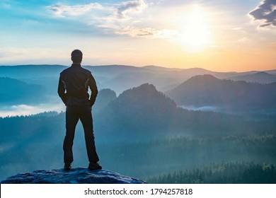 Wanderer beobachtet die Herbstsonne am Horizont. Schöner Moment. Spektakuläre Bergketten, Silhouetten. Der Mensch erreicht den Gipfel der Freiheit