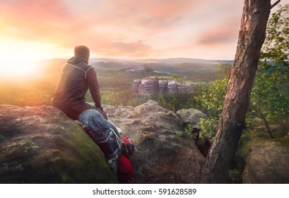 Hiker watching the beautiful landscape with a stunning sunset.
