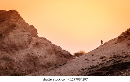 Hiker is watching sunset in Hajar Mountains of Ras Al Khaimah in UAE