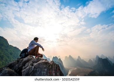 Hiker Watching sunset on the top of mountain. Xingping, Yangshuo, China.