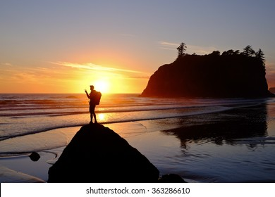 Hiker Watching Sunset at Over the Ocean Surf.  Ruby Beach, Olympic National Park, Washington.