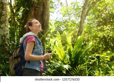 Hiker watching through binoculars wild birds in the tropical jungle. 