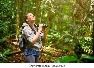 Hiker watching through binoculars wild birds in the jungle. Bird watching tours
