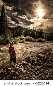 Hiker wearing checkered shirt stands near the Cimarron River Ouray Colorado