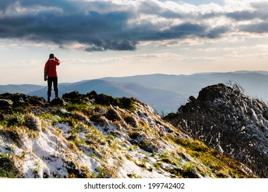 Hiker wearing a colorful jacket is enjoying the views from the top of Bieszczady mountain ridge