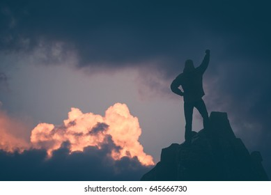 Hiker who conquered the top of mountain standing on a cliffs edge with raised hand against sunset sky. Instagram stylization.