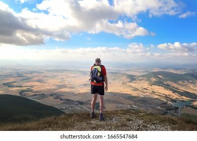 Un excursionista que ha llegado a la cima de la montaña toma una foto del valle debajo
