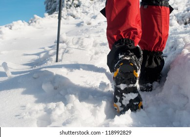 hiker in a winter mountain, trekking boots close-up