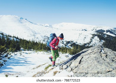 Hiker in winter mountains. Man with backpack trekking in mountains. Winter hiking.