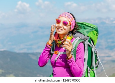 Hiker woman applying sun cream to protect her skin from dangerous uv sun rays high in mountains. Travel healthcare concept