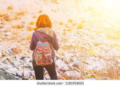 Hiker woman with backpack. A female tourist with a backpack, admiring the mountains, walking in the mountains in the summer.