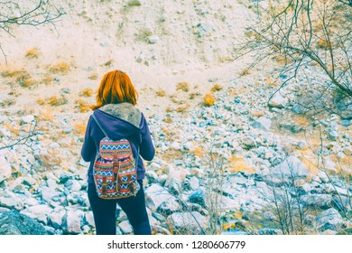 Hiker woman with backpack. Girl travel in mountains alone. Spring weather, calm scene.