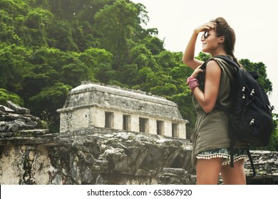 Hiker woman with backpack looking at ancient Mayan ruins