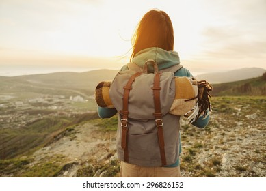 Hiker woman with backpack and sleeping bag walking in the mountains in summer at sunset