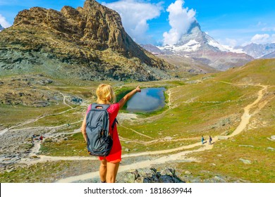 Hiker woman backpacker pointed Mount Matterhorn or Monte Cervino or Mont Cervin, and Swiss Alps and Riffelsee Lake. Activity outdoor in Zermatt, Canton of Valais, Switzerland, Europe.