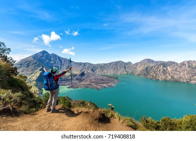 Hiker woman with blue backpack and trekking pole standing and enjoy with volcano Baru Jari Lake Segara Anak and Mount Rinjani summit view after finished climbing at Rinjani mountain. Lombok, Indonesia