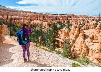 Hiker woman in Bryce Canyon taking a photo, looking and enjoying view during her hike wearing hikers backpack. Bryce Canyon National Park landscape, Utah, United States.