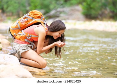 Hiker woman drinking water from river creek hiking in Zion National Park. Happy female hiker taking break drinking fresh water in Zion Canyon wearing backpack. Healthy lifestyle with girl in Utah, USA