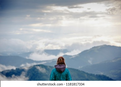 Hiker woman enjoying landscape of cloudy mountains, rear view