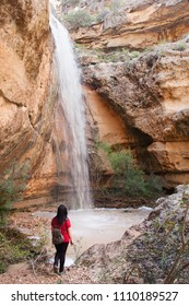 a hiker woman enjoying the view of a waterfall
