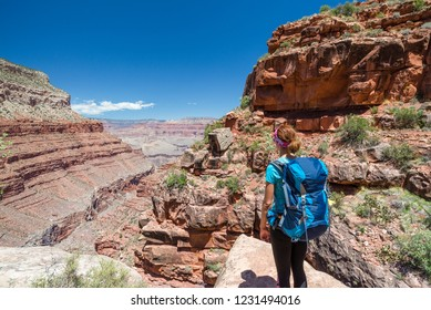 Hiker woman hiking in Grand Canyon. Healthy active lifestyle image of hiking young multiracial female hiker in Grand Canyon, Adventure and travel concept. Women hiking in USA national park.