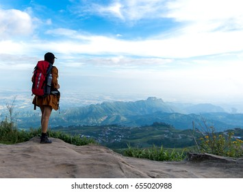 Hiker woman look binoculars on the mountain, background blue sky, Thailand, select and soft focus